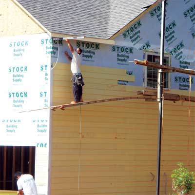 construction worker using an unsupported plank to reach the corner of a building far from the scaffold the board is attached to