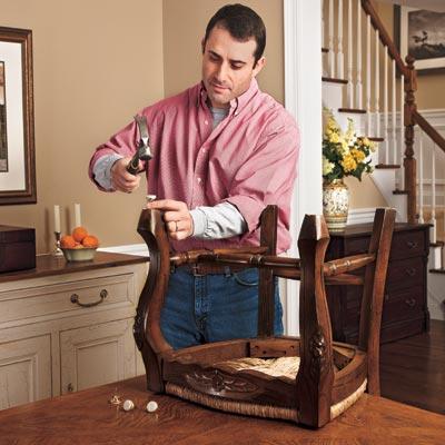 man hammering tacks with felt pads onto bottom of chair leg