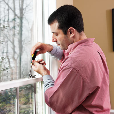 man fixing window that rattles in the wind