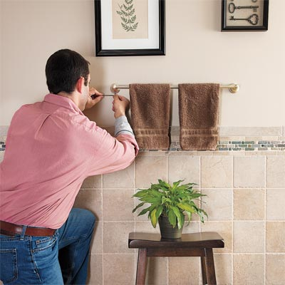 man tightening loose towel rack