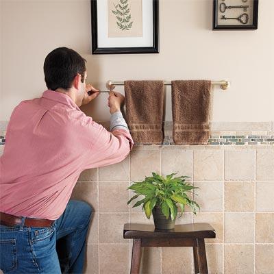 man tightening loose towel rack