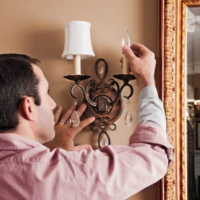 man screwing in sconce bulb