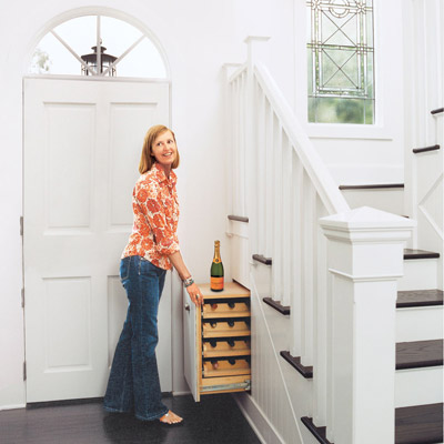 woman pulling out an under the stairs wine rack in her foyer