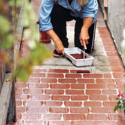 woman rolling paint on walkway to create effect of bricks