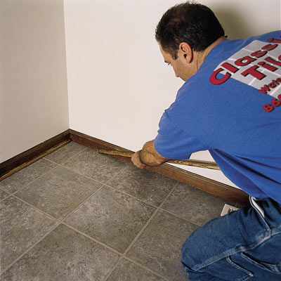 man laying a vinyl tile floor