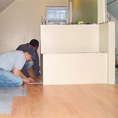 men working on installing built in storage bench in remodeled attic