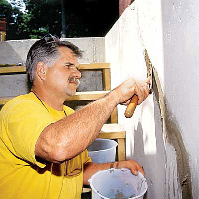 Tom Silva applies hydraulic cement to a foundation wall