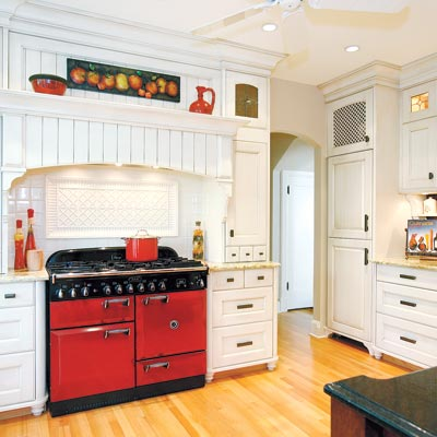 old world style kitchen with white cabinetry and red range