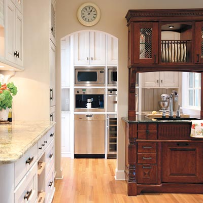 old world style kitchen with arched doorway to pantry with stainless steel appliances