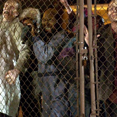 land of the dead scene of zombies in front of chain link fence