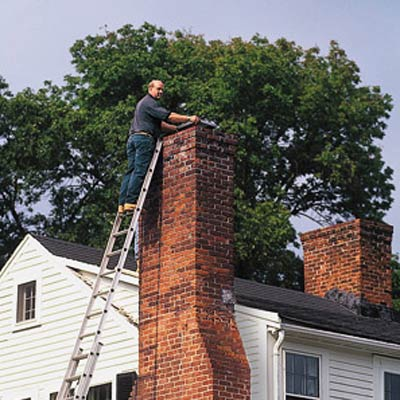 A man on a ladder repairing a chimney