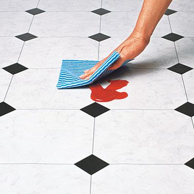 hand wiping up spill on vinyl flooring