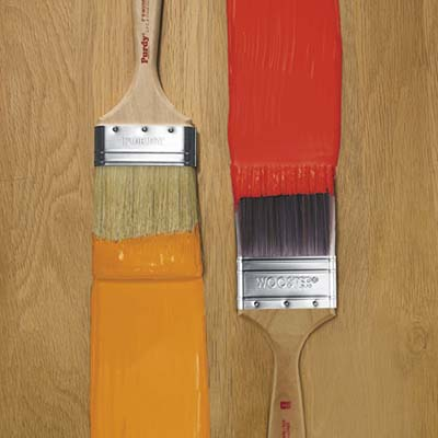 paint brushes dipped in red and orange paint