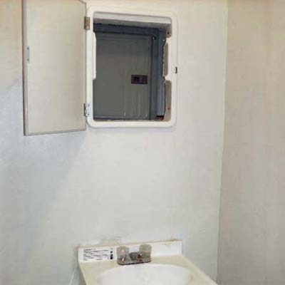 electrical panel mounted behind bathroom mirror