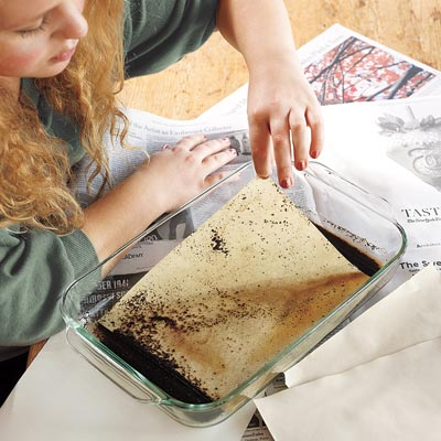 woman dyeing paper stationary with old coffee grounds and water