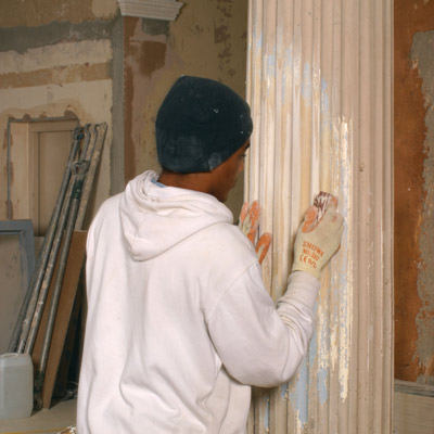 man stripping paint from column
