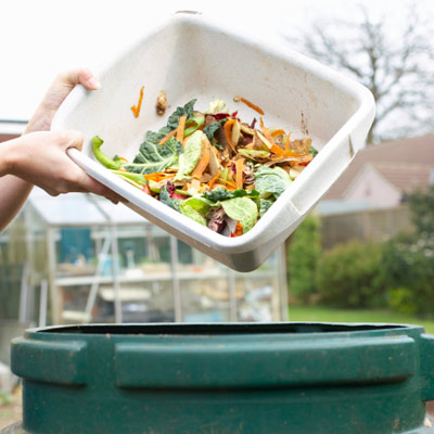person dumping food scraps into compost pin