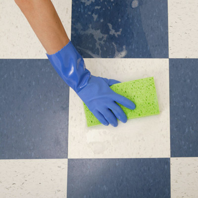 person scrubbing a tile floor with a sponge