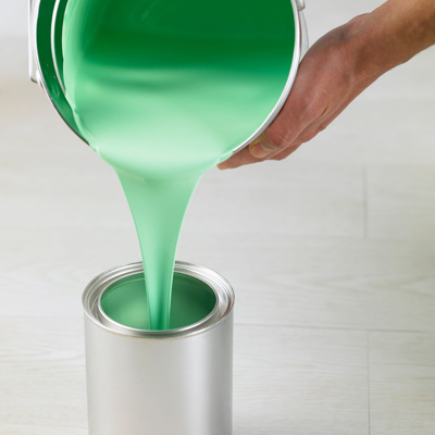 person pouring paint into a new paint can