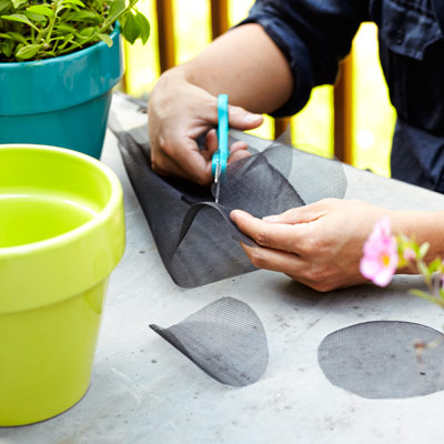 person cutting window screen scraps to fit in flower pots