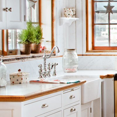 coastal cottage kitchen with close up of deep apron sink, and vintage-style faucet and drawer pulls