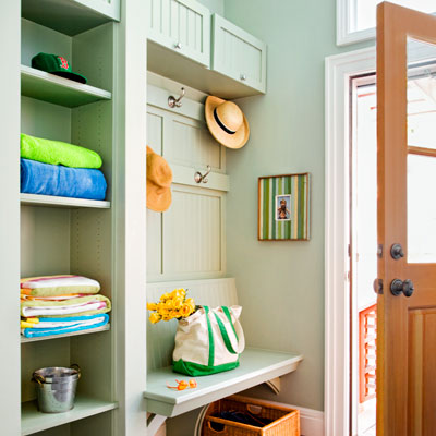 cottage style entryway turned mudroom with shelves, bench and tilt-up cabinet doors