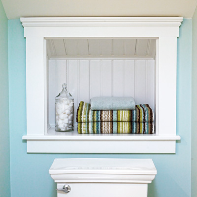 cottage style built-in bathroom storage cubby lined with beadboard