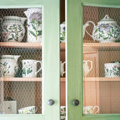 cottage style cabinets with chicken wire behind glass fronts