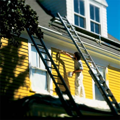 person on scaffold painting exterior of house yellow