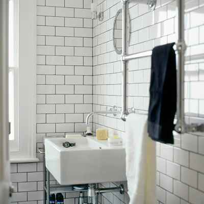 bathroom wall with white ceramic subway tile and black grout