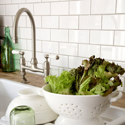kitchen sink and backsplash with white ceramic subway tile and gray grout