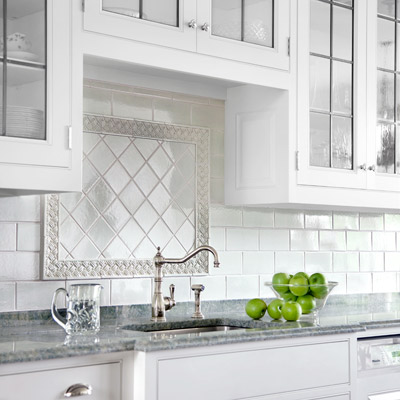 kitchen with all-white subway backsplash, border of floral tile surrounding square tile in diamond pattern