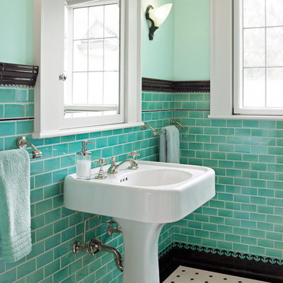 bath with teal gloss ceramic subway tile with black base and a chair-rail
