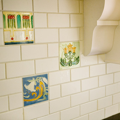 ornamental square tiles scattered throughout white gloss subway tile