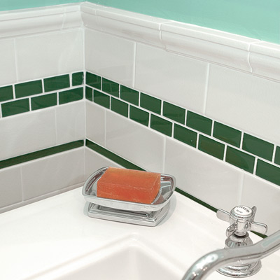 bath with green liner and white subway tiles, green mosaic tiles band