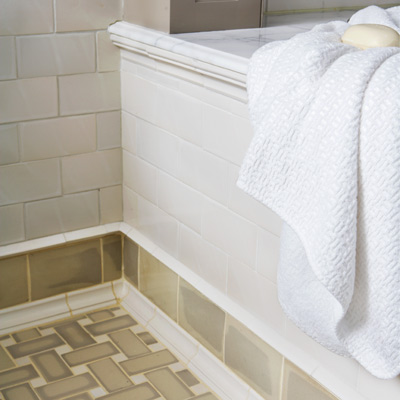 bath with floor tile, subway tile between rows of shoe-molding trim and knife-edge liner