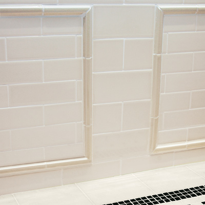 wall with half-round trim pieces mimic wainscot in wall frames on top of subway tile