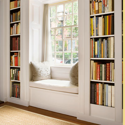 window seat in home office between built-in bookcases