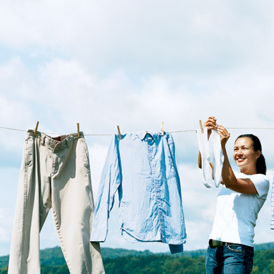 woman hanging up clothes on an old-fashioned clothesline outside
