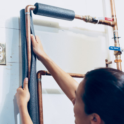 woman putting insulation around hot water pipes