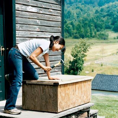 woman building a worm bin in her garden