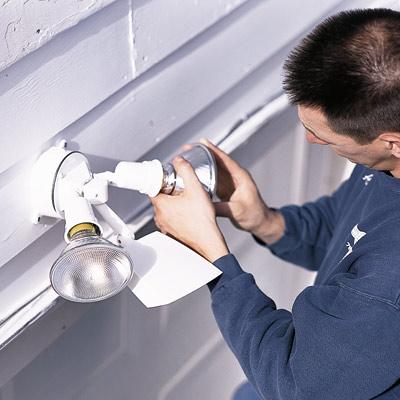 man installing sensor on all-night garage floodlight