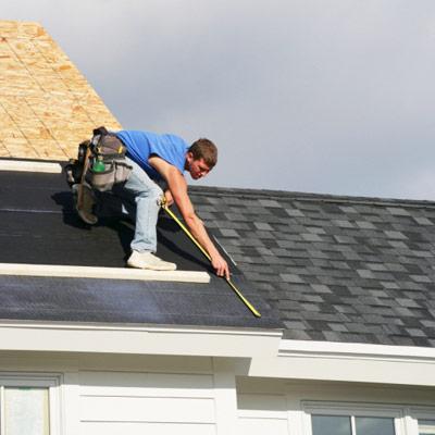man installing roofing shingles