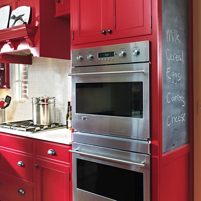 wall ovens in red Shaker-style flat-panel cabinets with wall blackboard message center