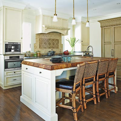 neutral kitchen with a walnut countertop, gray-olive woodwork and tumbled tile backdrop