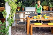 a woman sets a table in an outdoor kitchen/dining area