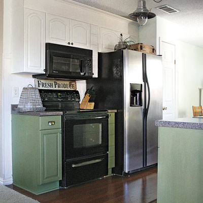 farmhouse-style kitchen after remodel with green cabinets, black appliances