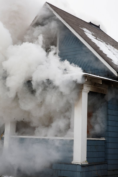 smoke from house fire escaping through house windows