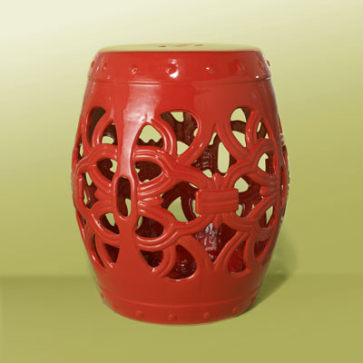 a Chinese red garden stool with curved cutouts