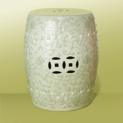 a white ceramic garden stool with a green vine pattern
